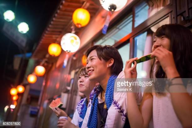 スイカを食べた地元の祭りのパフォーマンスを見て若い女性 - 伝統行事 ストックフォトと画像
