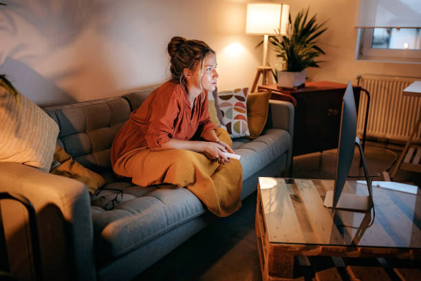 young women watching tv at home - watching your tv at night stock pictures, royalty-free photos & images