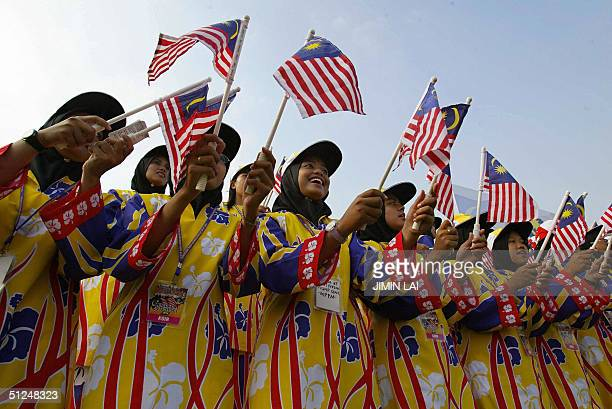 Young women wearing colourful costumes wave Malaysian flags during the National Day celebrations in the eastern town of Kuantan 31 August 2004...