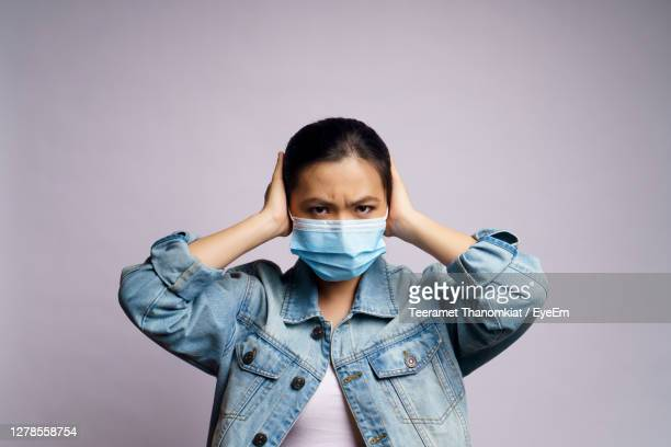 young women wearing face mask against wall - infectious disease stock pictures, royalty-free photos & images