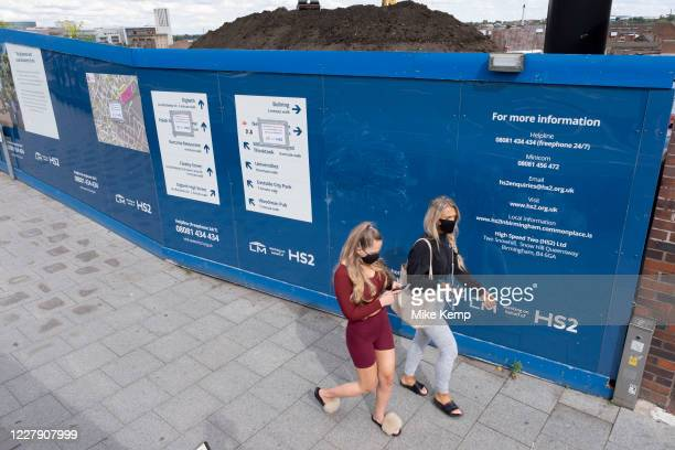 Young women wearing face masks pass the construction site hoardings for the HS2 mainline station at Curzon Street on 3rd August 2020 in Birmingham,...