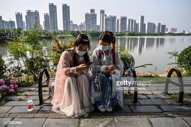 Young women wearing facemasks and traditional costumes of Song dynasty and Tang dynasty are seated on a bench in a park next to the East Lake in...