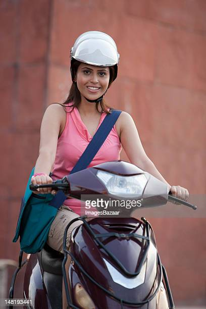 Young women wearing helmet while driving motor scooter