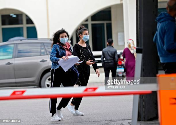 Young women wearing protective masks walk out of the Rafik Hariri University Hospital in the southern outskirts of the Lebanese capital Beirut on...