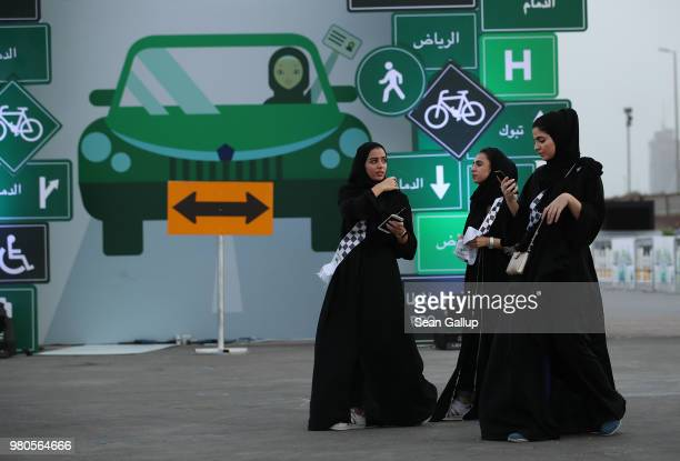 Young women wearing the traditional abaya walk past a sign as they help to organize an outdoor educational driving event for women on June 21 2018 in...