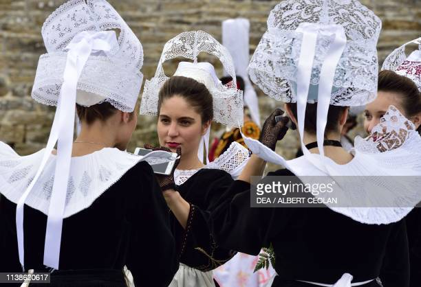 Young women wearing traditional costumes and Coiffe Bigoudene Festival of Blue Nets Concarneau Brittany France
