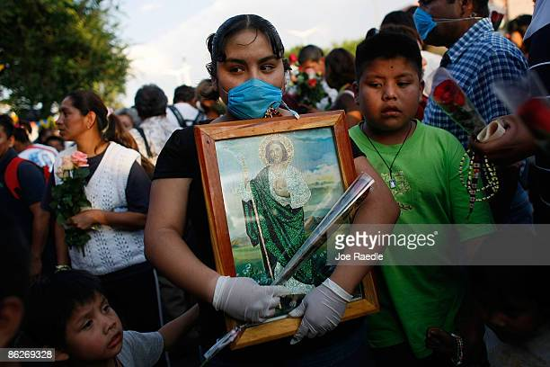 A young women wears a surgical mask to help prevent being infected with the swine flu as she holds a religious picture on April 28 2009 in Mexico...