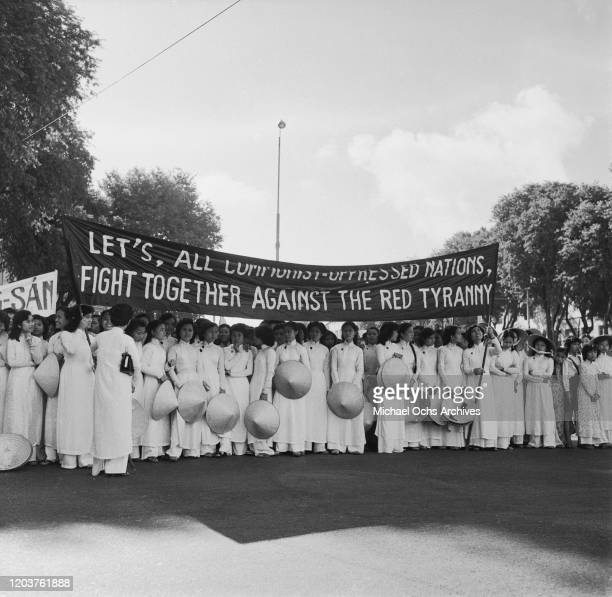 Young women with a banner reading 'Let's, All Communist-Oppressed Nations, Fight Together Against The Red Tyranny' at an anti-Communist demonstration...