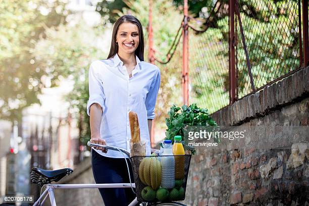 young women with a basket of healthy food - fahrradkorb stock-fotos und bilder