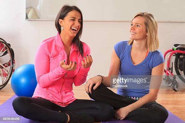 Young women with a spinal cord injuries and with their wheelchairs having fun in a yoga studio