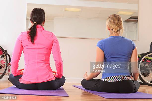 Young women with a spinal cord injuries doing a yoga meditation pose in a studio