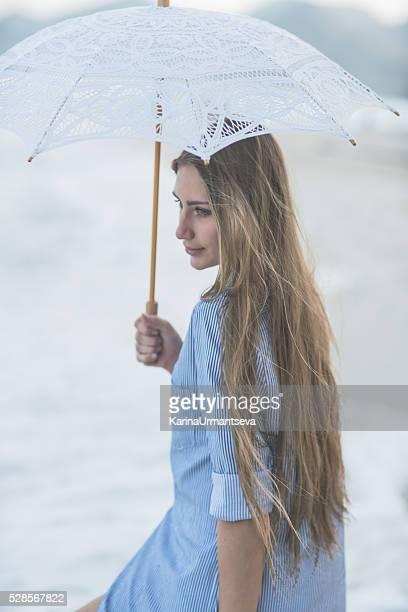 Junge Frauen mit einem Regenschirm am Strand