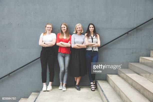 Junge Frauen mit Armen stehend auf Treppen durch Betonwand gekreuzt