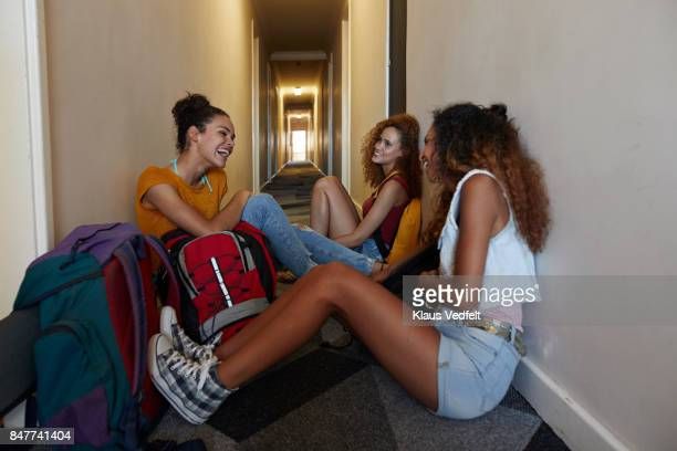 Young women with backpacks sitting and waiting on the isle of youth hostel
