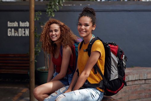 Young women with backpacks smiling, while sitting in courtyard - gettyimageskorea