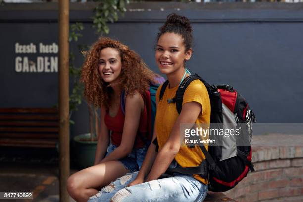 Young women with backpacks smiling, while sitting in courtyard