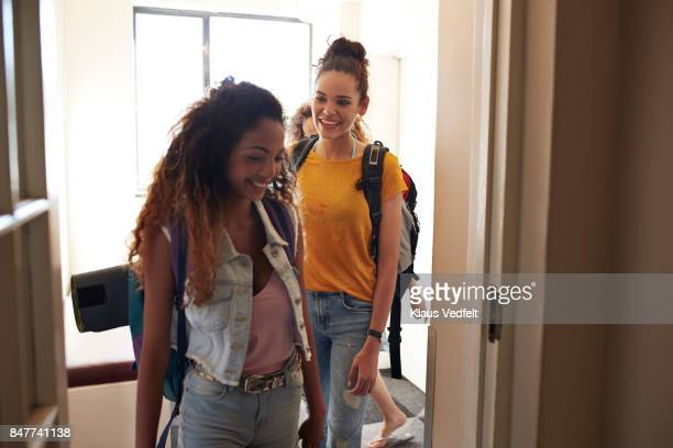 young women with backpacks, walking on isle of youth hostel - ankunft stock-fotos und bilder