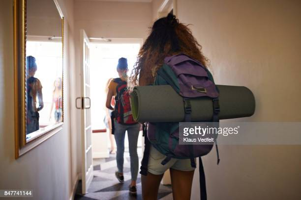 Young women with backpacks, walking on isle of youth hostel