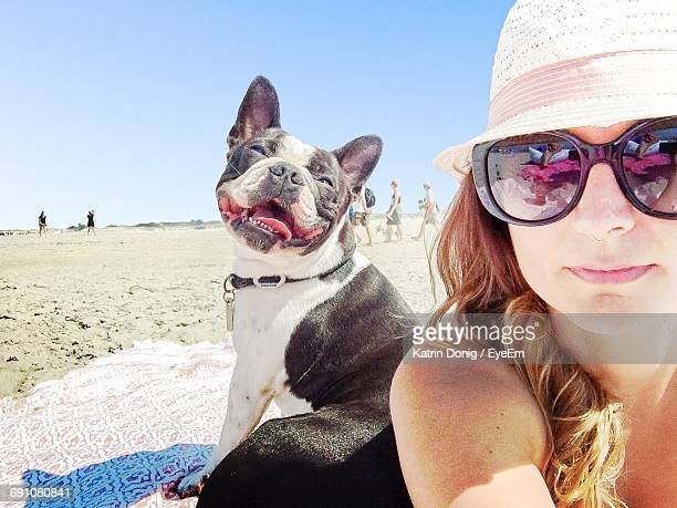 Young Women With Boston Terrier Enjoying At Beach