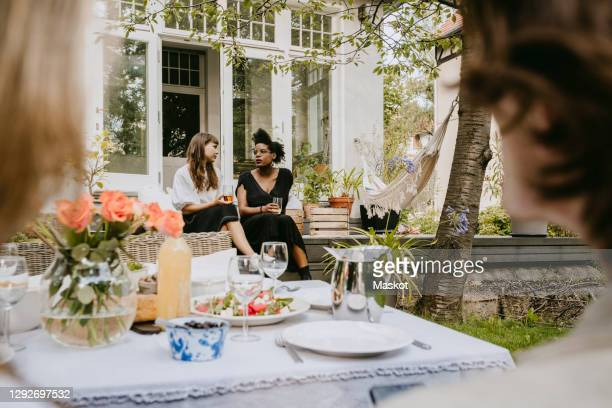 young women with drinking glass talking while sitting in backyard - four people stock pictures, royalty-free photos & images