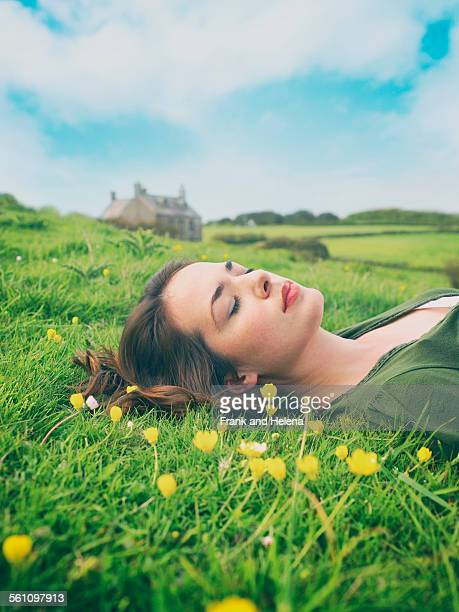 Young women with eyes closed lying in buttercup grass