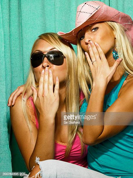 Young women with hands on lips in photo booth