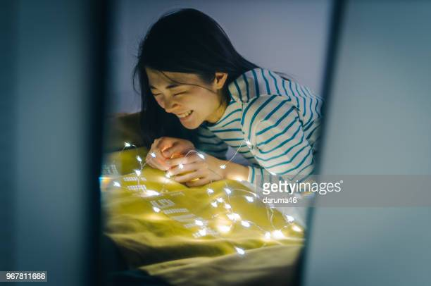 Young women with LED in bedroom.