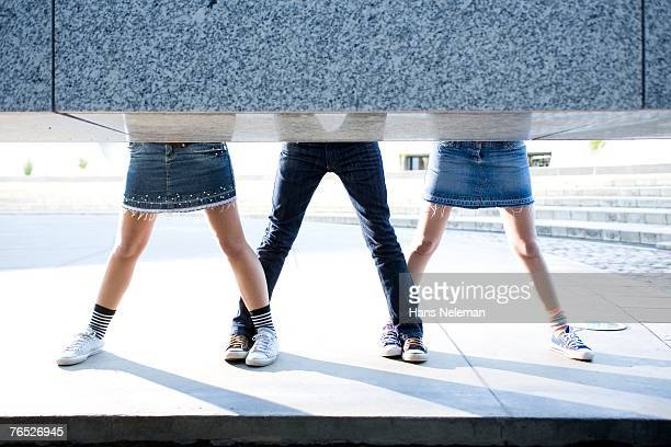 Young women with legs apart in sneakers, low section