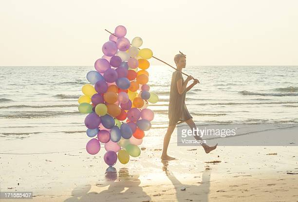 young women with multicolored balloons at beach