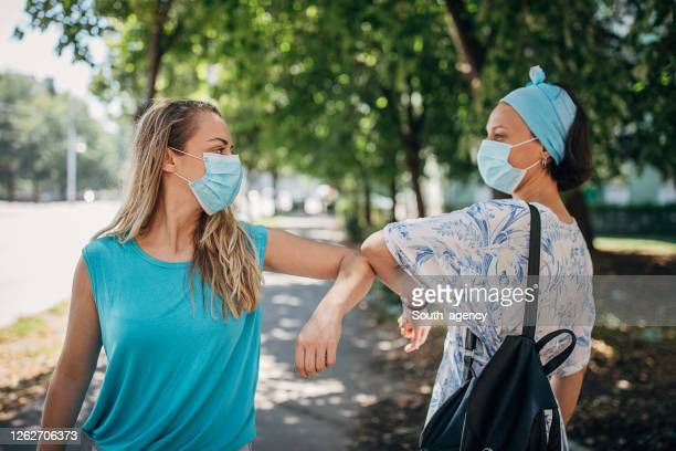 young women with protective face masks greeting with elbows - female friendship stock pictures, royalty-free photos & images
