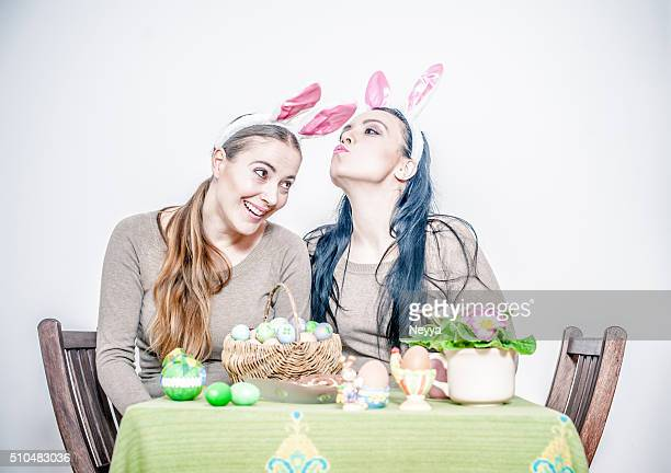 Young women with rabbit ears having fun with easter eggs