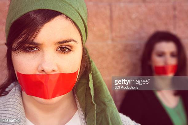 young women with red tape over mouths in protest - fury stock pictures, royalty-free photos & images