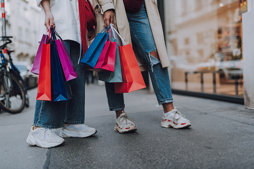 Young women with shopping bags standing on the street 1148923865