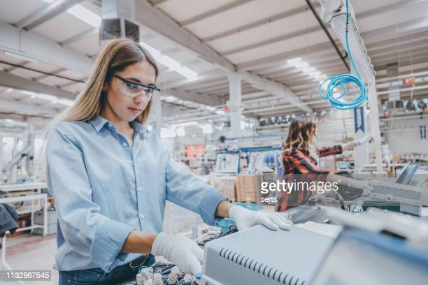 young women working on the production line in factory - electronics industry stock pictures, royalty-free photos & images