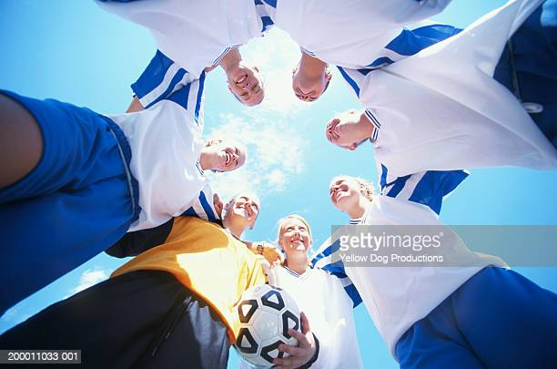 Young women's soccer team forming huddle, view from below