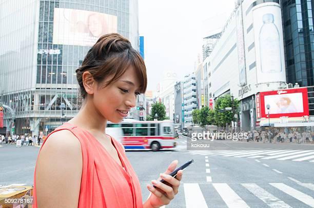 若い womon チェック、スマートフォンで、渋谷スクランブル交差点