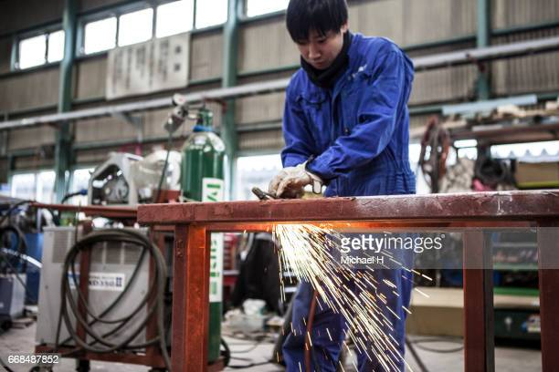 Young worker cutting steel items at factory