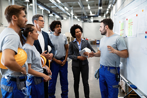 Young worker giving presentation in front of whiteboard in a factory. 1151863802