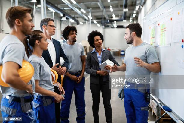 Young worker giving presentation in front of whiteboard in a factory.