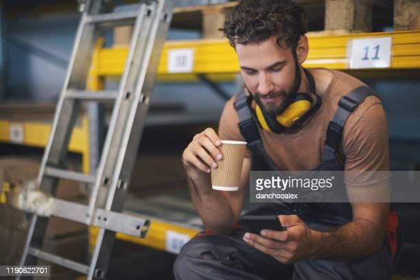 junge arbeiterin im lager macht eine pause - pause machen stock-fotos und bilder