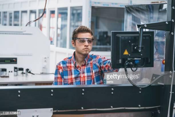 junger arbeiter mit computer in industrieller produktionslinie - rechnerunterstütztes konstruieren stock-fotos und bilder
