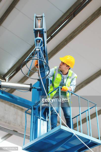 young worker man working with industrial wire handling equipment in factory - instruction manual stock photos and pictures