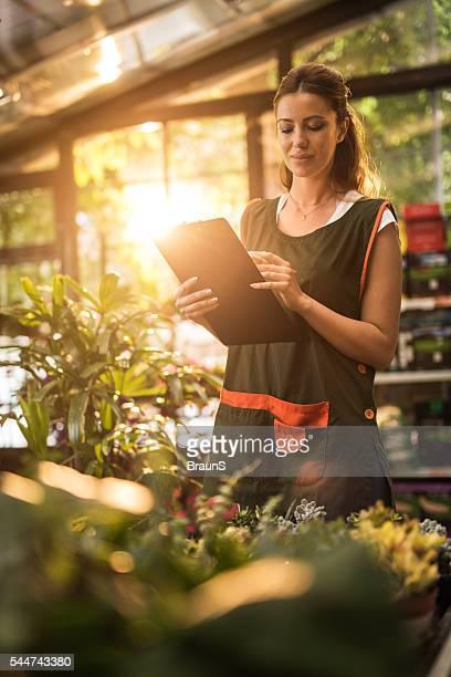 Jovem trabalhador tomar notas em um jardim centro.