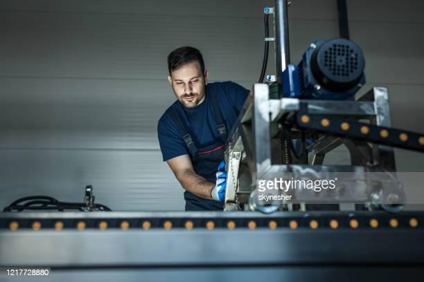 junge arbeiter, die an einer produktionslinie maschine in einer fabrik arbeiten. - maschinenbau stock-fotos und bilder