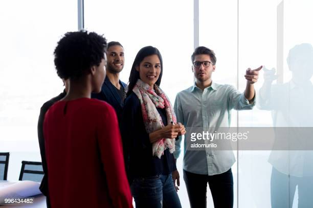 jovens trabalhadores em pé olhando para placa - casual chic - fotografias e filmes do acervo