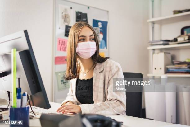 young working businesswoman looking over from her office desk to her colleagues - mlenny stock pictures, royalty-free photos & images