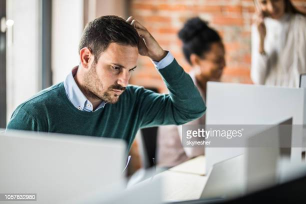 young worried businessman working on laptop at corporate office. - worried stock pictures, royalty-free photos & images
