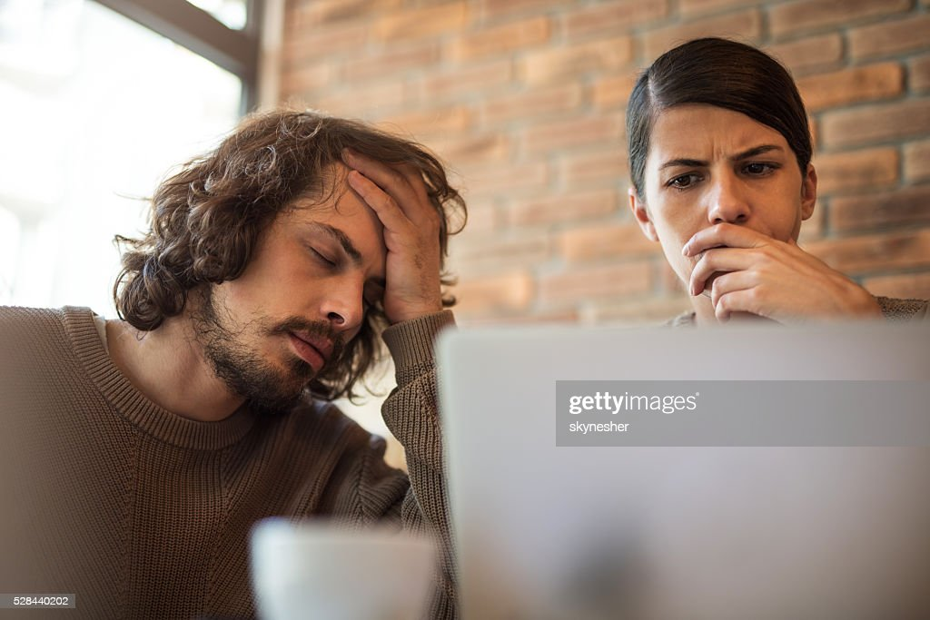 Young worried couple at home using laptop. : Stock Photo