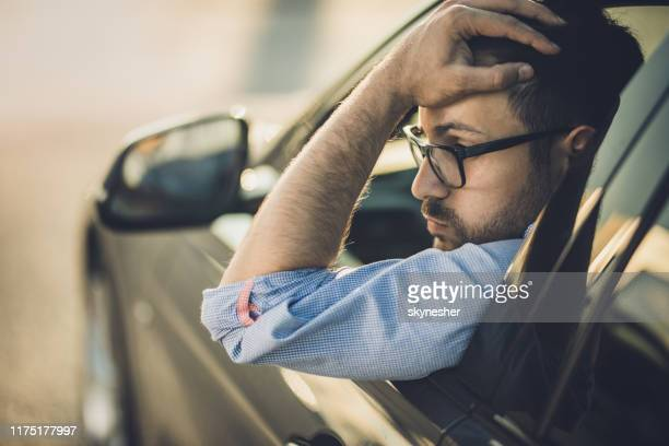 young worried man having problems in a car. - driving stock pictures, royalty-free photos & images