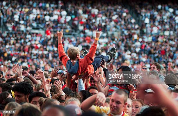 A young worshipper 'surfs' across the crowd during a highenergy Christian rock performance as America's best known evangelist 84yearold Billy Graham...